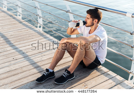 stock-photo-attractive-young-male-athlete-sitting-on-pier-and-drinking-water-448177264